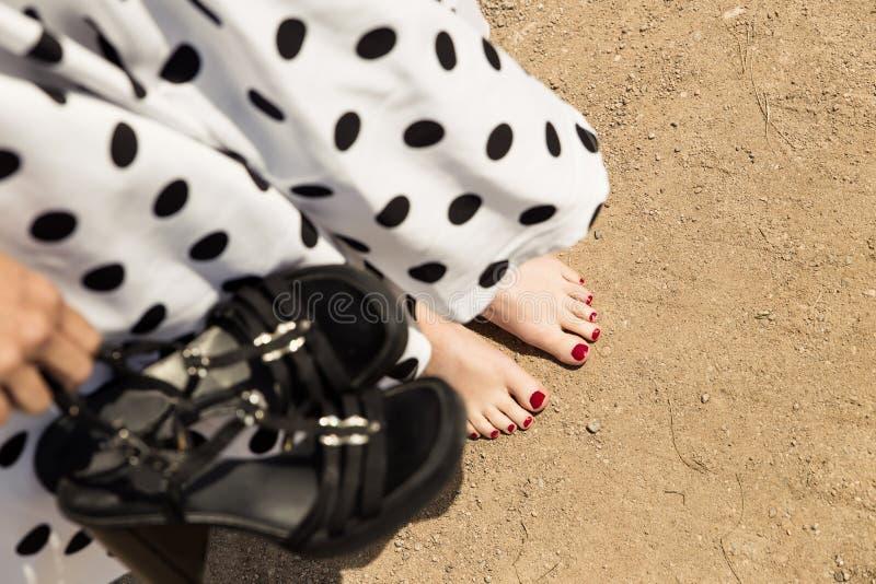 Женщина в белизне поставила точки платье держа ее ботинки, barefoo крупного плана стоковое изображение rf