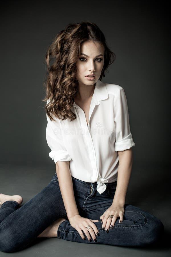 Женщина в белой блузке и голубых джинсах стоковые фотографии rf