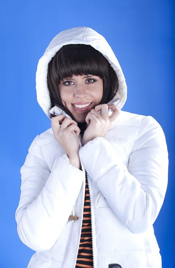 Женщина в белой куртке на голубой предпосылке стоковое фото rf