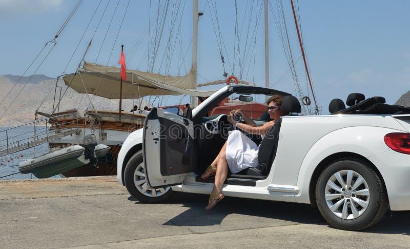 Женщина в белом автомобиле с откидным верхом стоковые изображения rf