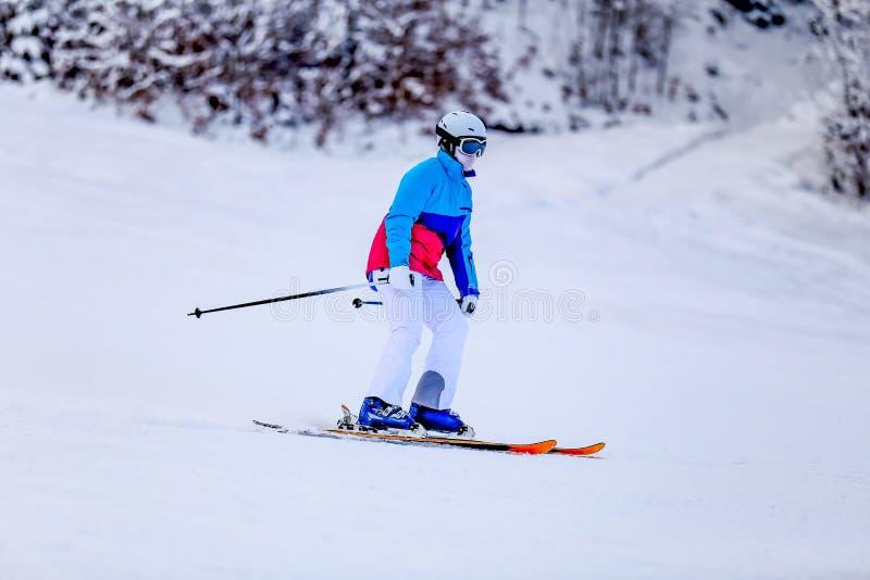 Женщина в белом костюме катания на лыжах на наклоне горы стоковая фотография rf
