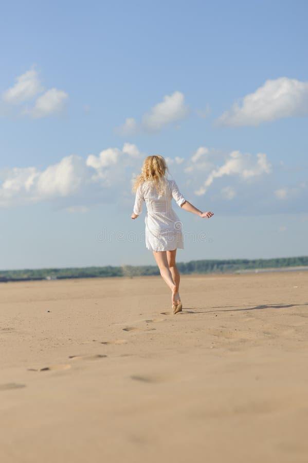 Женщина в белый скакать платья стоковые фото