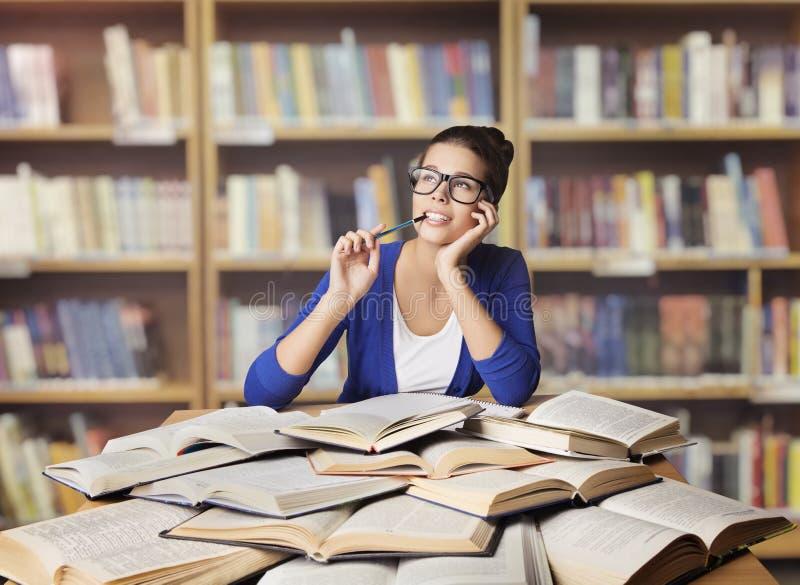 Женщина в библиотеке, книгах студента раскрытых исследованием, изучая девушку стоковое фото rf