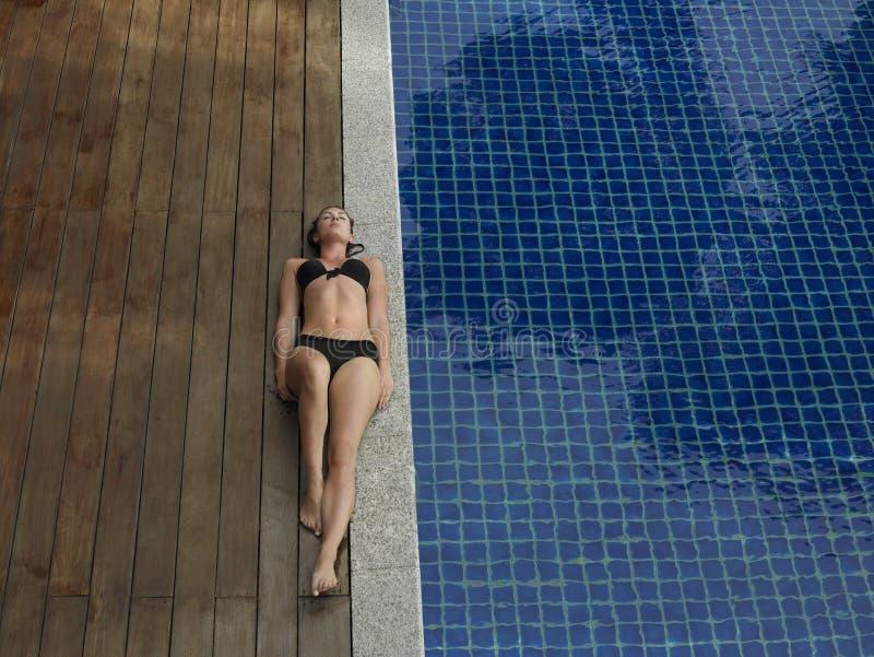 Женщина в бикини лежа бассейном стоковые изображения rf