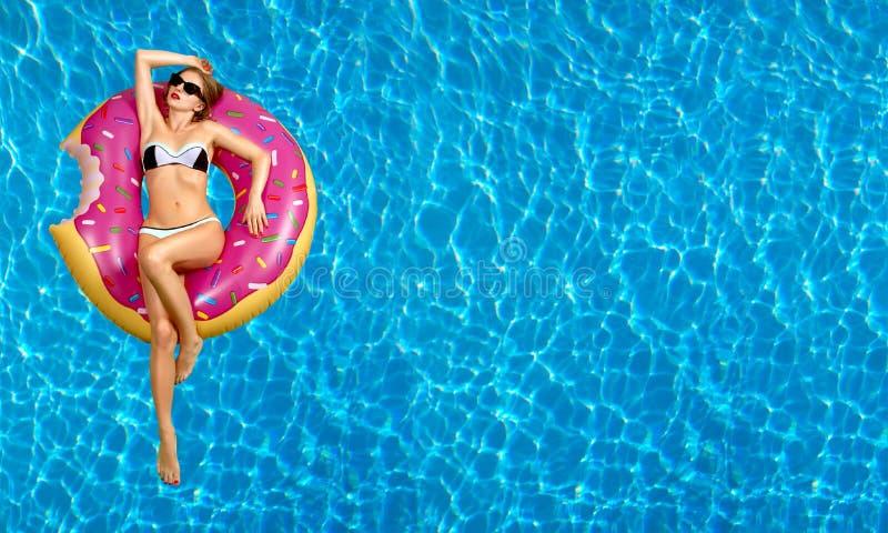 Женщина в бикини на раздувном тюфяке в бассейне стоковая фотография rf