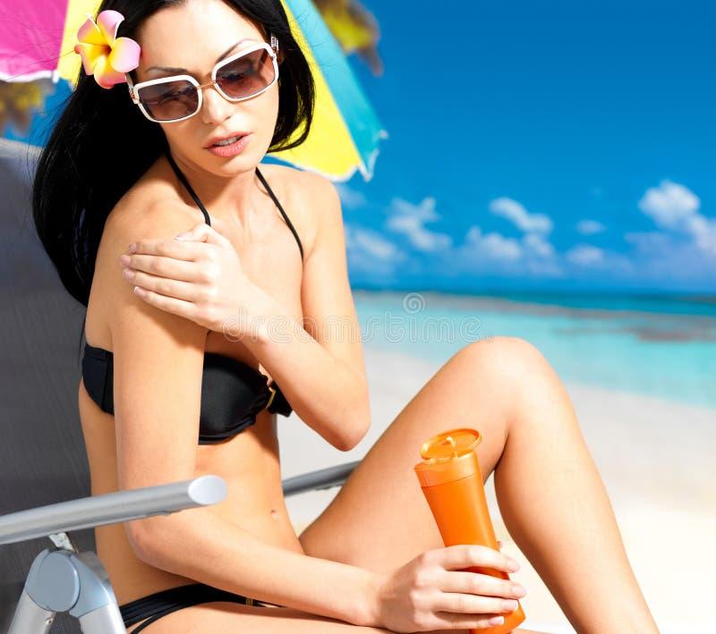 Женщина в бикини прикладывая сливк блока солнца на теле стоковая фотография