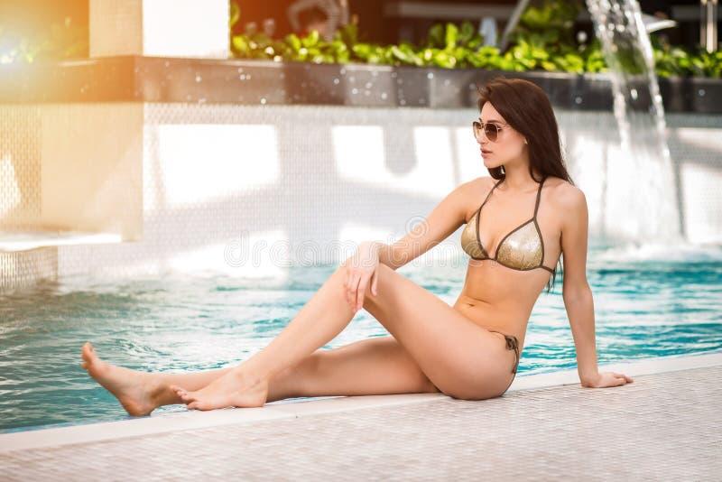 Женщина в бикини сидя бассейном стоковая фотография rf
