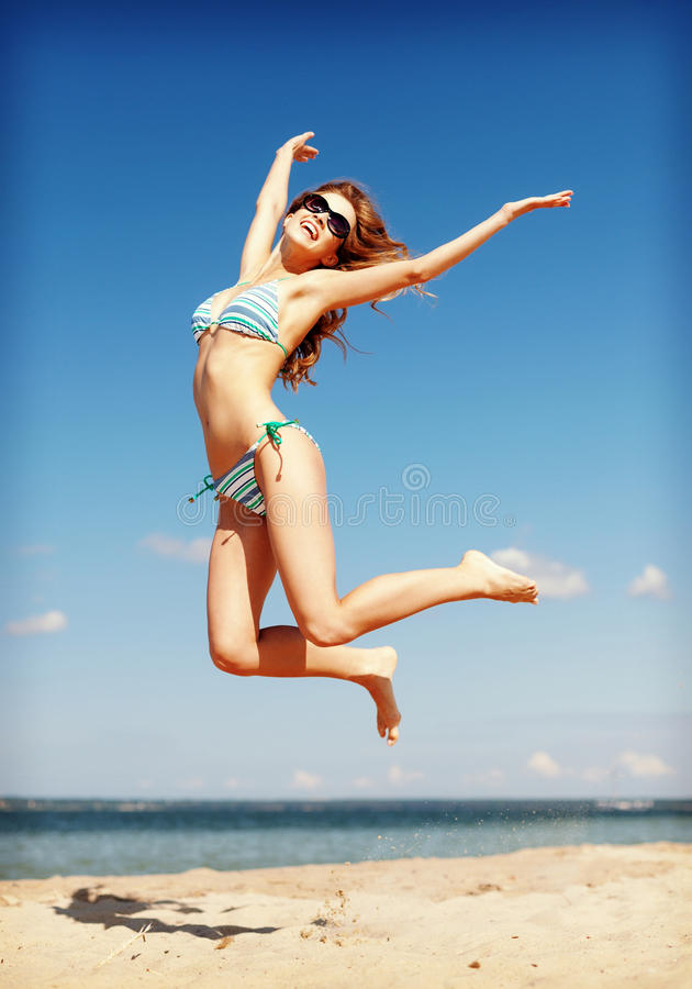Женщина в бикини скача на пляж стоковые фото