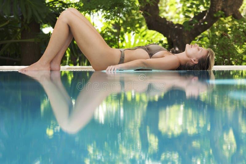 Женщина в бикини спать бассейном стоковые изображения rf