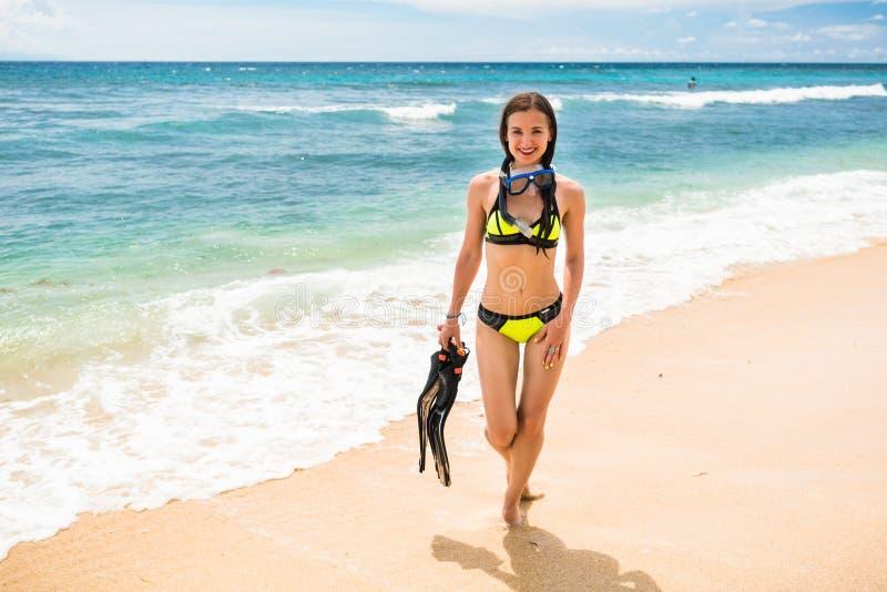 Женщина в бикини с snorkelling шестерней идет на пляж стоковая фотография