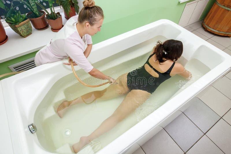 Женщина в ванне во время гидромассажного в салоне курорта красоты стоковые фотографии rf