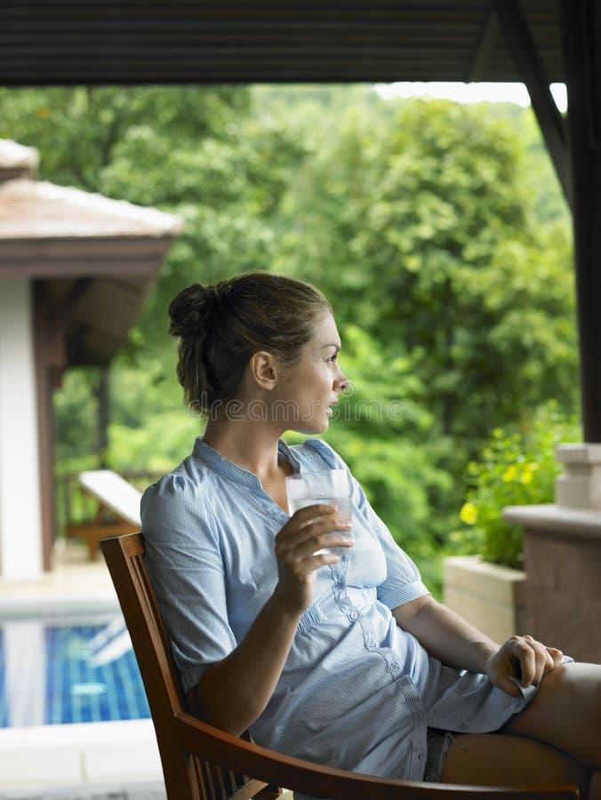 Женщина в веранде с стеклом воды стоковое фото rf