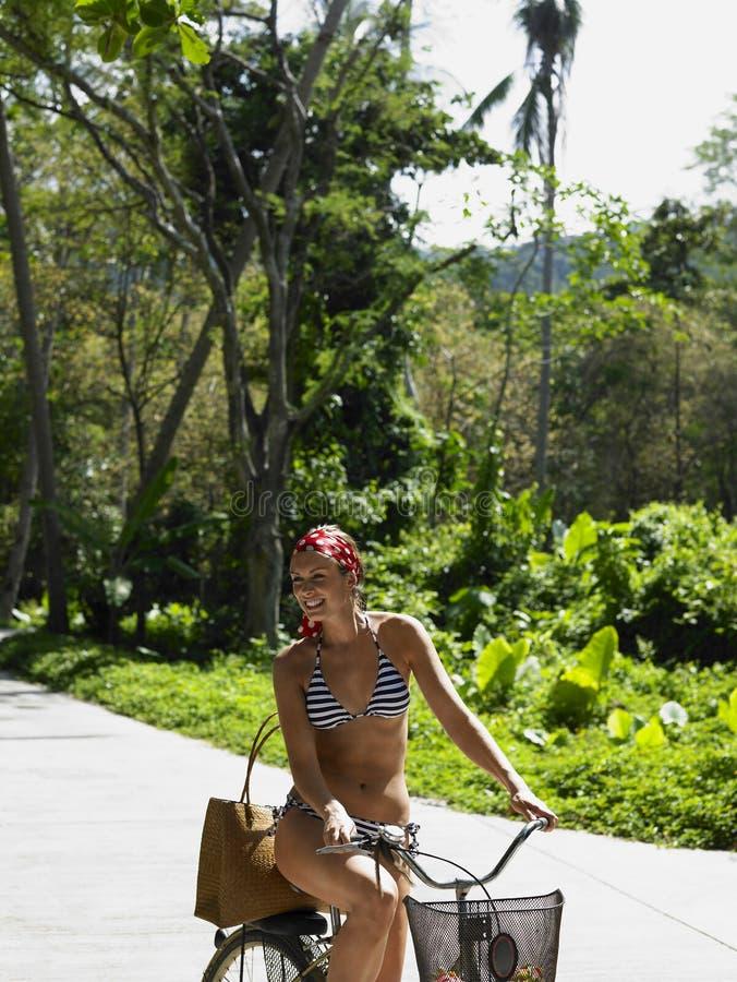 Женщина в велосипеде катания бикини стоковое изображение