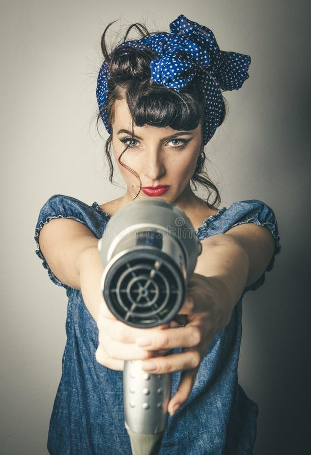 Женщина в винтажных одеждах указывая фен для волос стоковое изображение