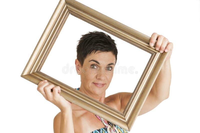 Женщина в вкосую держа рамке стоковое фото