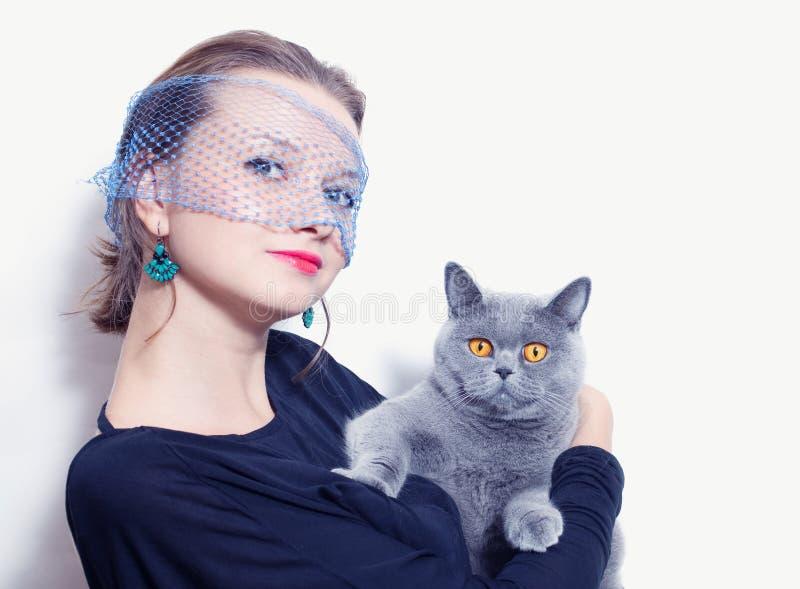 Женщина в вуали держа серого великобританского кота стоковые изображения