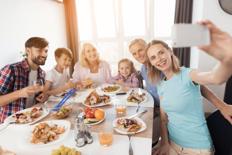 Женщина в голубой футболке делает selfie на белом smartphone Ее семья сидит за ей на праздничной таблице стоковое изображение rf