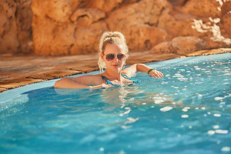 Женщина в голубом купальнике и солнечных очках ослабляя в открытом бассейне с чистой прозрачной водой бирюзы стоковое фото