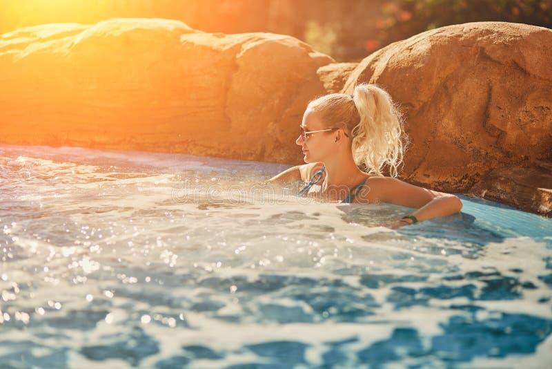Женщина в голубом купальнике ослабляя в джакузи на открытом воздухе с чистой прозрачной водой бирюзы Пирофакел Солнця стоковые изображения