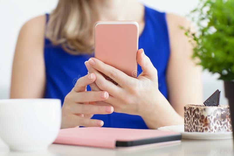 Женщина в голубом платье в кафе держа розовый телефон стоковое изображение rf