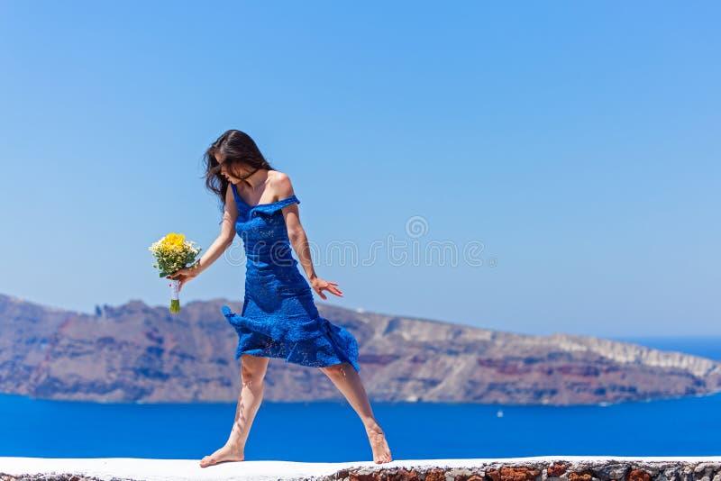 Женщина в голубых танцах платья в море стоковая фотография