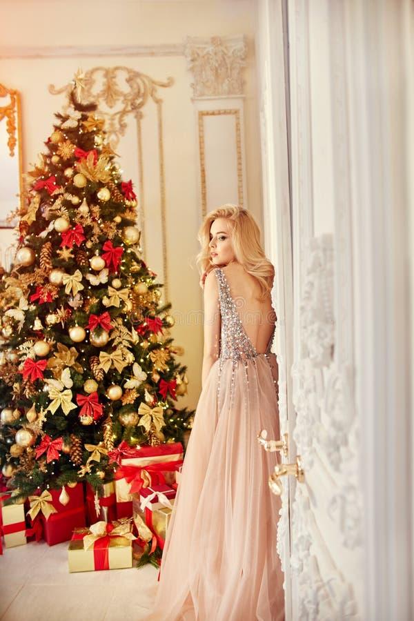 Женщина в длинном цвета сливк платье, стоящ около рождественской елки и двери Роскошная блондинка в платье вечера празднует стоковое фото rf