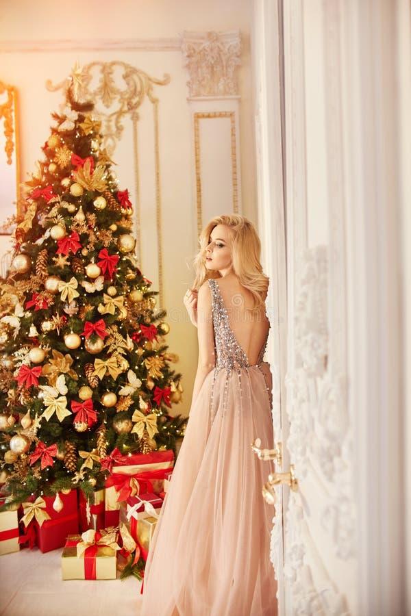 Женщина в длинном цвета сливк платье, стоящ около рождественской елки и двери Роскошная блондинка в платье вечера празднует стоковое фото
