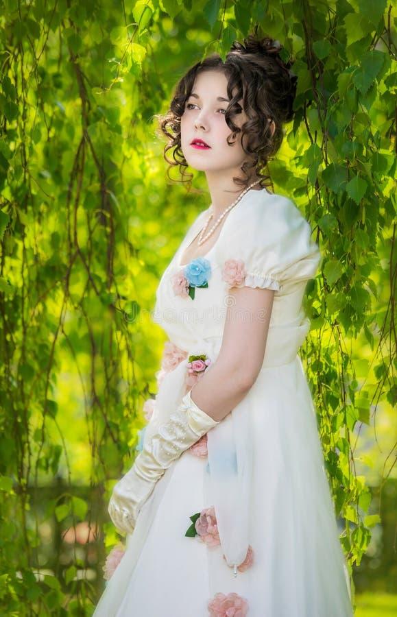 Женщина в длинном, элегантном белом платье невесты в парке стоковые изображения
