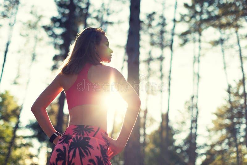 Женщина в лесе, нося умный вахта привлекательной пригонки атлетическая, принимая пролом от интенсивной разминки Спорт, фитнес, ра стоковое изображение