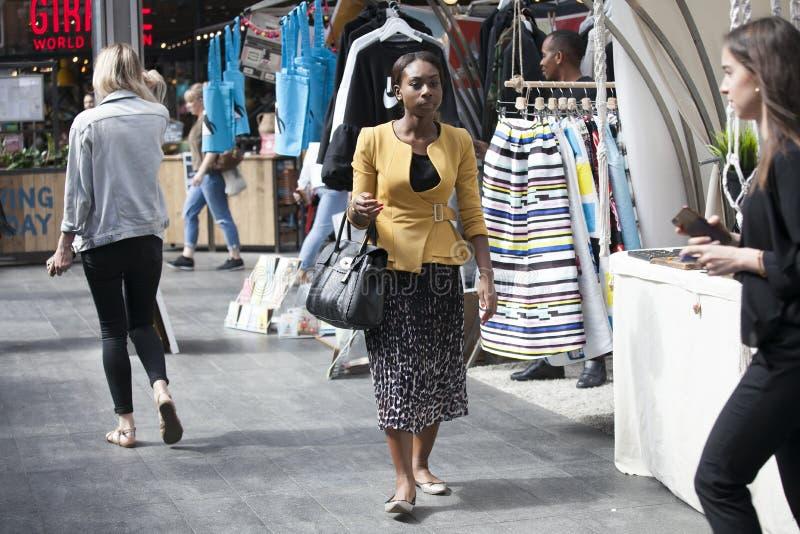 Женщина в желтой фуфайке и пестротканой юбке идет через рынок стоковые фотографии rf