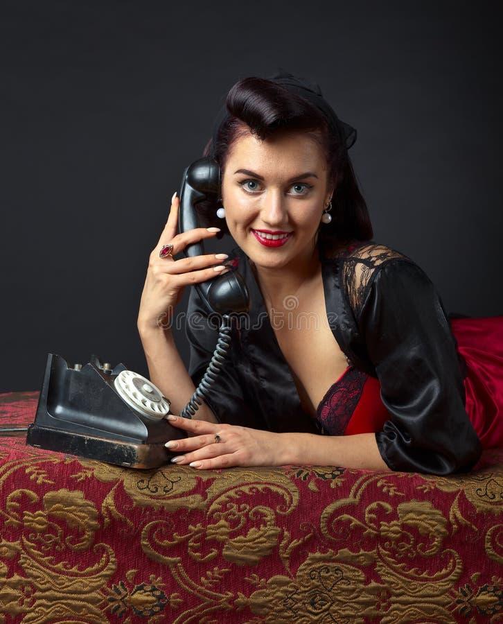 Женщина в женское бельё с старым телефоном стоковое фото rf