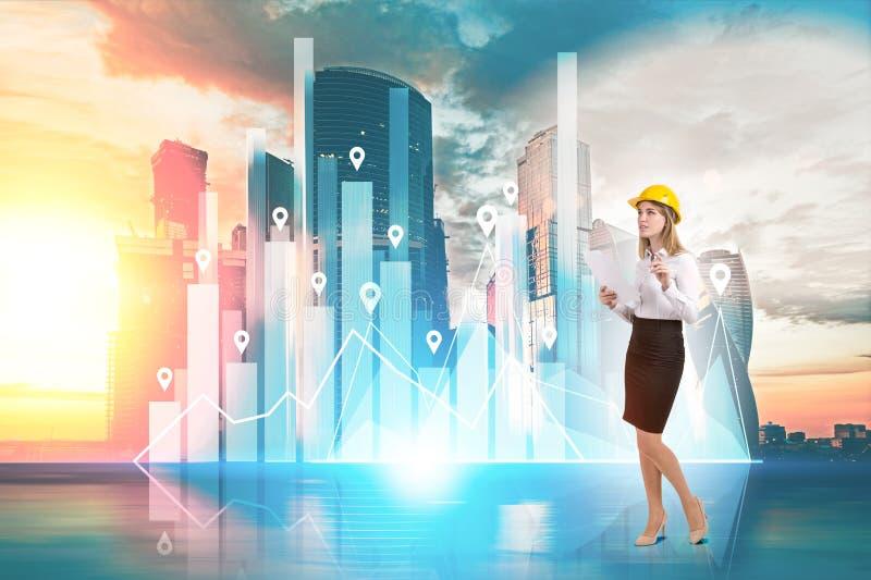 Женщина в желтой трудной шляпе и диаграмма против городского пейзажа стоковая фотография