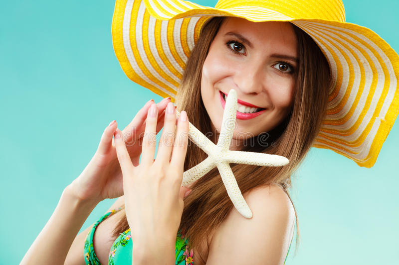 Женщина в желтой шляпе держа белую раковину стоковые фото
