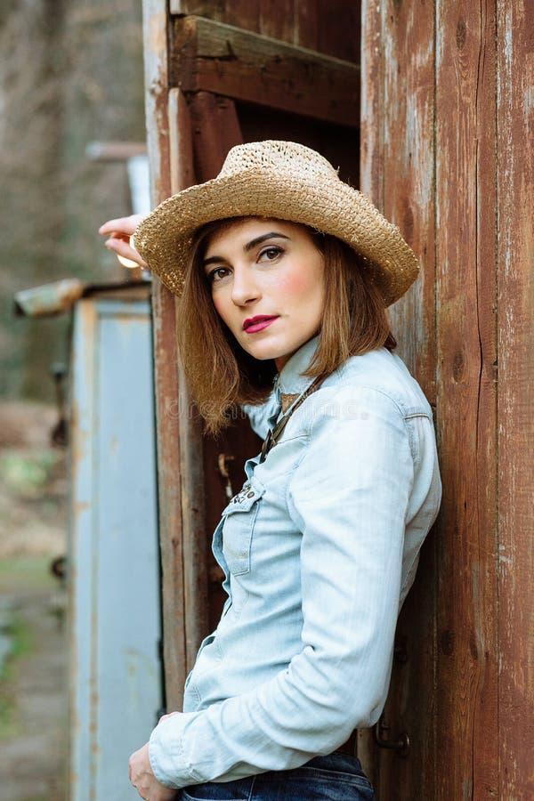 Женщина в западной носке в ковбойской шляпе, джинсы и ботинки ковбоя стоковое фото