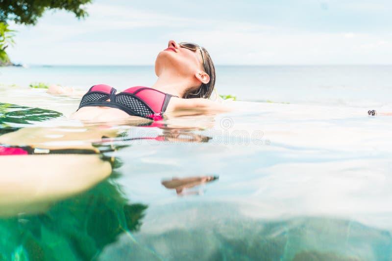 Женщина в заплывании каникул расслабляющем в бассейне стоковая фотография rf