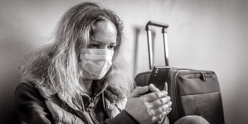 Женщина в защитной медицинской маске сидит возле багажа в аэропорту Новая вспышка коронавируса COVID-19, эпидемия в Вухане, Китай стоковая фотография
