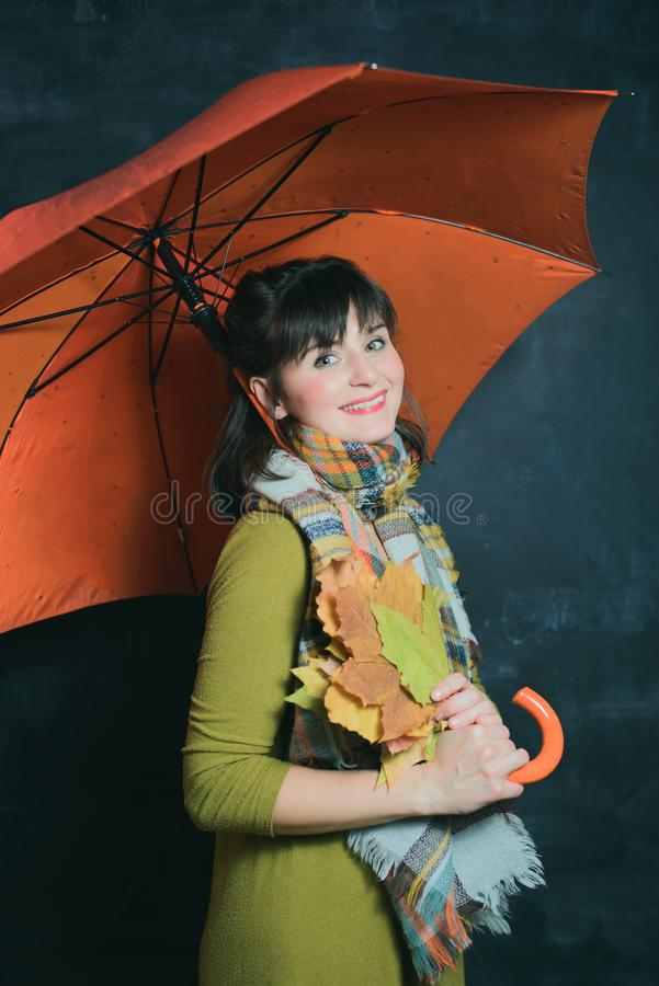 Женщина в зеленом платье держит листья под оранжевым зонтиком стоковое фото rf