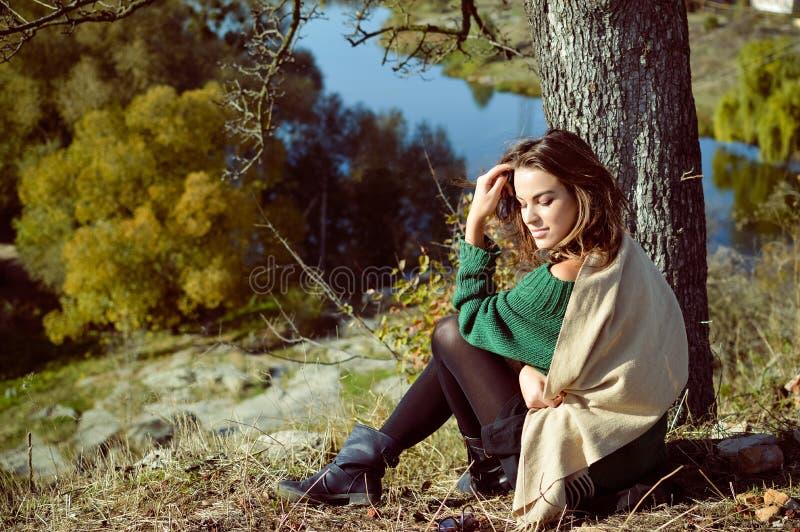 Женщина в зеленом пуловере сидя под деревом стоковые изображения rf