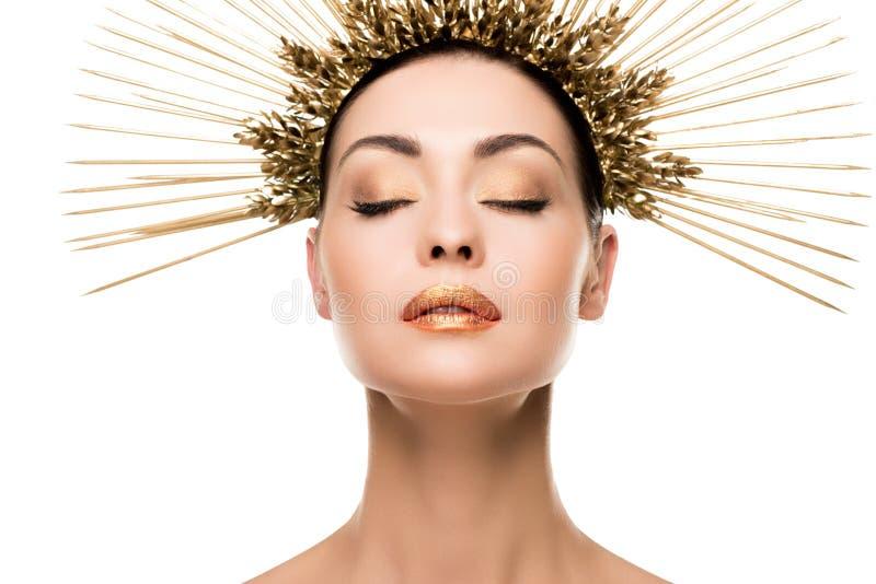 Женщина в золотой заставке представляя при закрытые глаза изолированные на белизне стоковые изображения