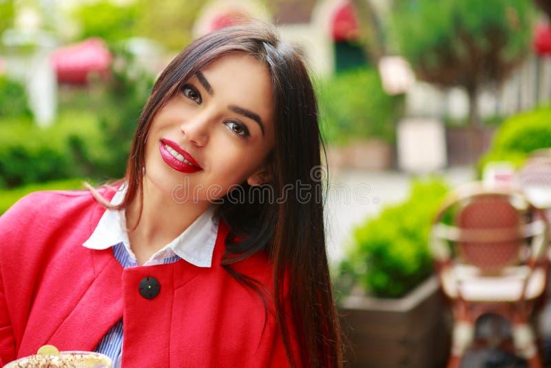 Женщина в камере кофейни кафа счастливой усмехаясь смотря стоковое фото rf