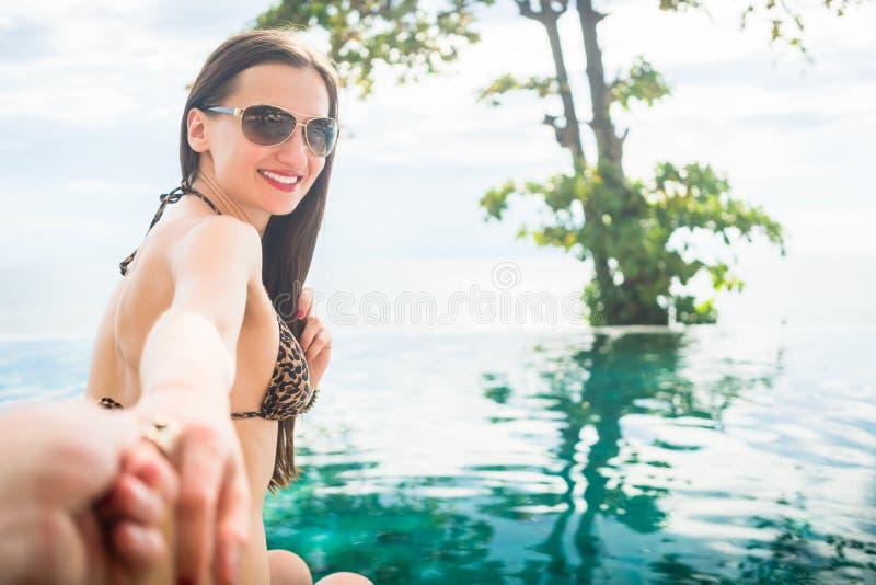 Женщина в каникулах волочит человека в бассейне морем стоковая фотография rf