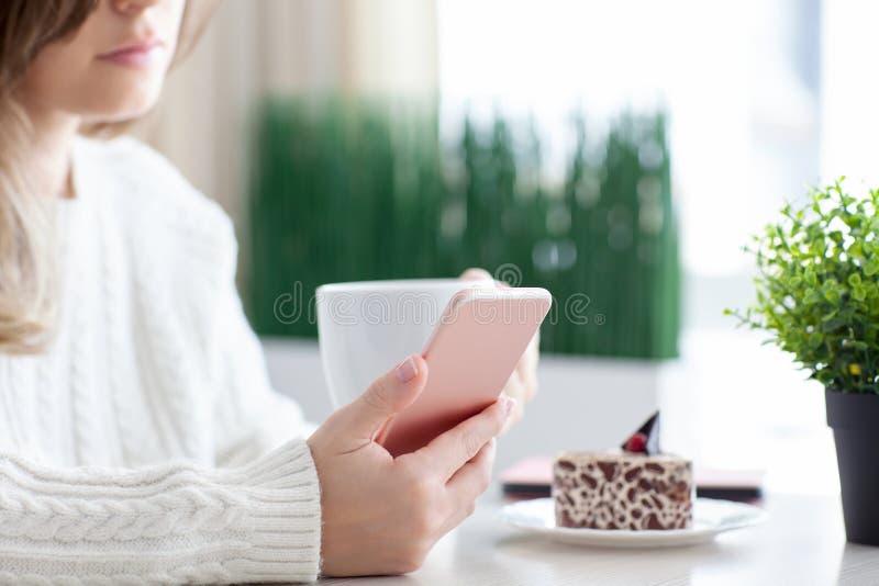 Женщина в кафе и держать кафа выпивая розовый телефон стоковая фотография rf
