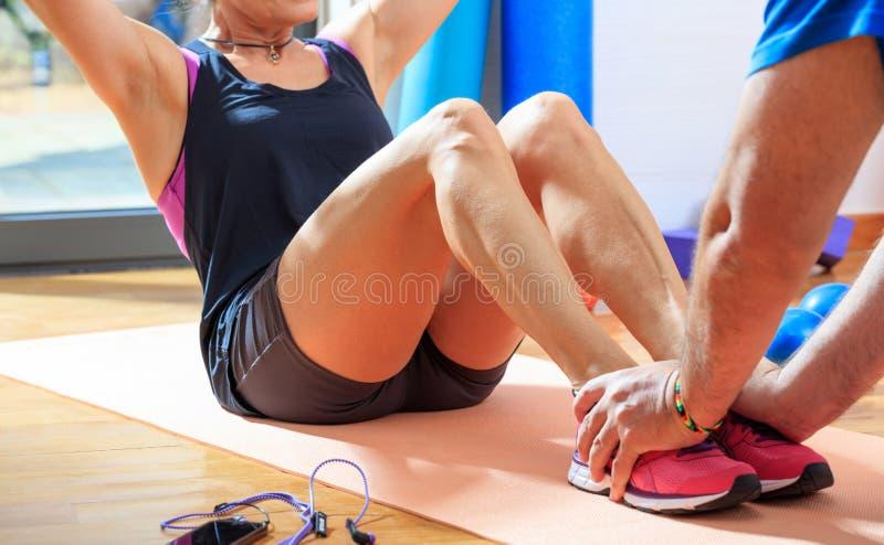 Женщина в классе фитнеса делая abdominals стоковая фотография rf