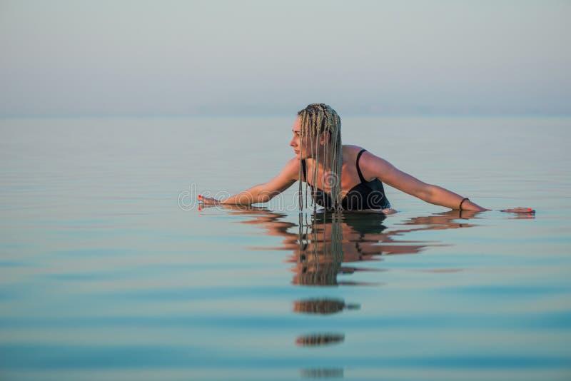 Женщина в костюме заплыва наслаждается морской водой штиля на море стоковая фотография