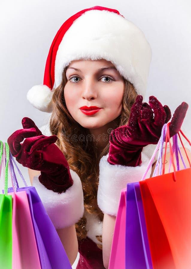 Женщина в костюме Санта Клауса держит хозяйственные сумки стоковые изображения rf