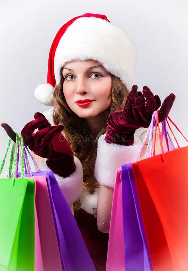 Женщина в костюме Санта Клауса держит хозяйственные сумки стоковые фотографии rf