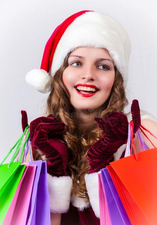 Женщина в костюме Санта Клауса держит хозяйственные сумки стоковое фото