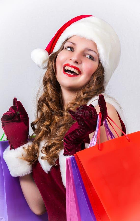 Женщина в костюме Санта Клауса держит хозяйственные сумки стоковое изображение