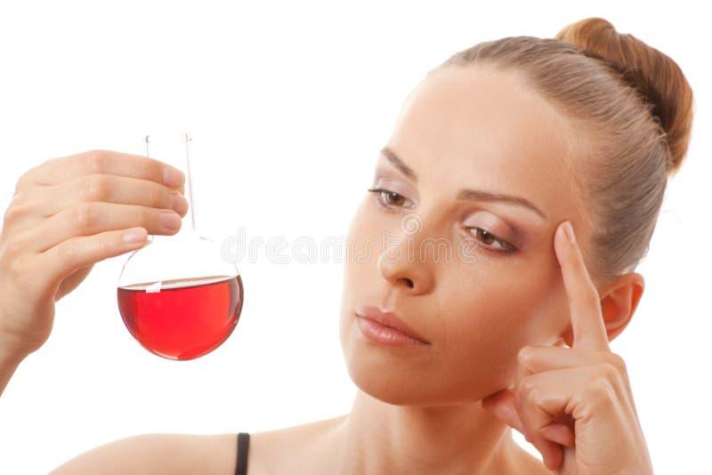 Женщина в костюме спорт держит склянку с красной жидкостью стоковое изображение