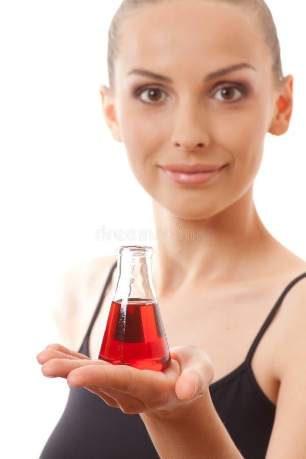 Женщина в костюме спорт держит склянку с красной жидкостью стоковые изображения rf